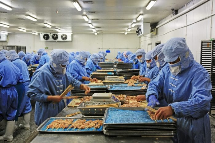 Workers in a meat processing production line wearing PPE